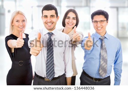 Business team holding their thumbs up - stock photo