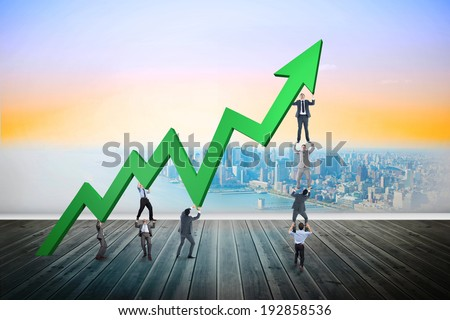 Business team holding up arrow against city projection on wall - stock photo