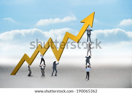 Business team holding up arrow against cloudy landscape background - stock photo