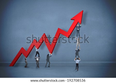 Business team holding up arrow against dark room - stock photo