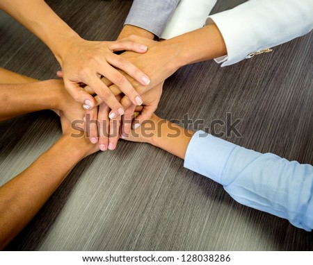 Business team in a meeting with their hands together - stock photo
