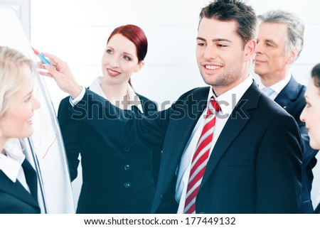 Business - team in an office, a colleague is standing in front of the flipchart - stock photo