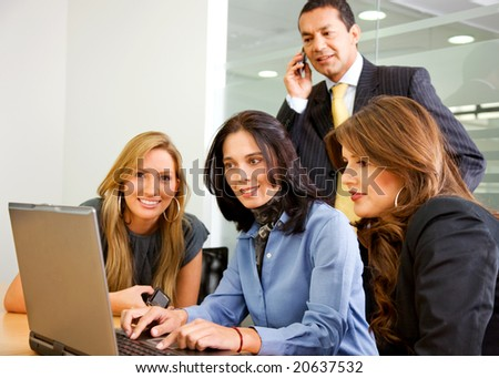 business team in an office meeting on a laptop computer - stock photo