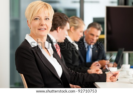 Business - team in an office; the female boss is looking into the camera - stock photo
