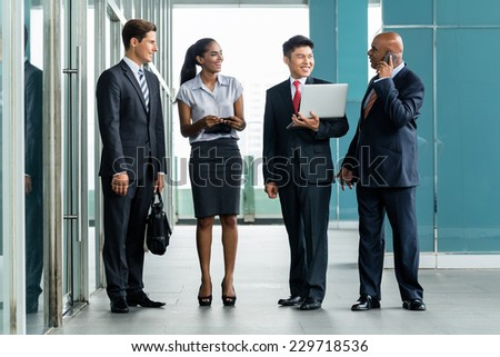 Business Team in front af Bank facade discussion project reporting to Indian CEO - stock photo