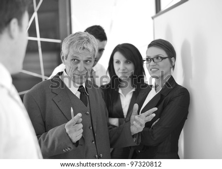 business team in the office in front of a board - stock photo