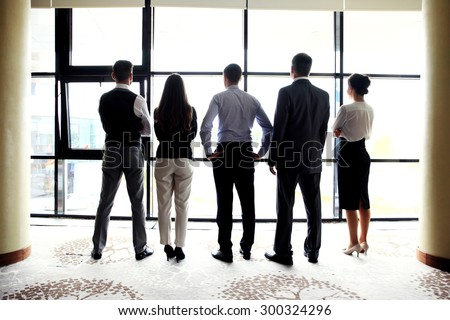 Business team looking at city through window - stock photo