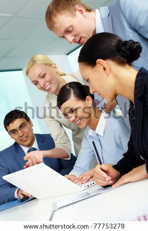 Business team looking at laptop screen while planning work at meeting - stock photo