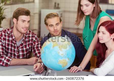 Business team looking for global markets as they plan the expansion of their business sitting around a table in the office with a globe - stock photo