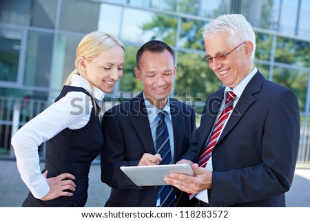 Business team looking together at a tablet computer - stock photo