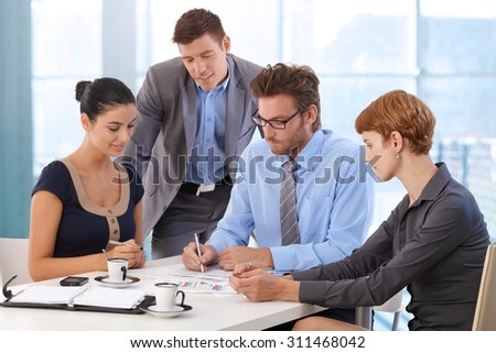 Business team meeting at office table with boss. Writing on paper, wearing suit and glasses, sitting at table, businessman, businesswoman, personal organizer, morning coffee. - stock photo