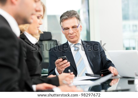 Business - team meeting in an office, the boss is checking his mails - stock photo