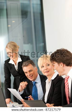 Business - team meeting in an office with laptop, the boss with his employees - stock photo