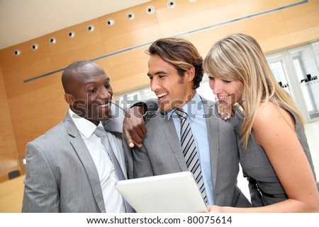 Business team meeting in congress center with electronic tablet - stock photo