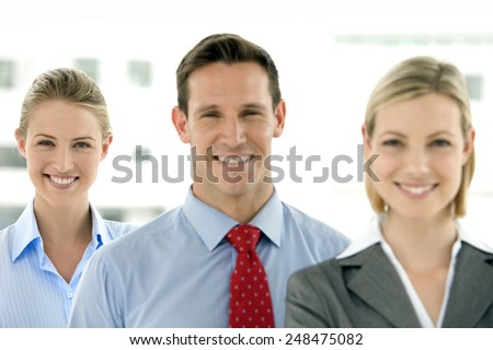 Business team of a businessman and two businesswomen standing in a row - stock photo