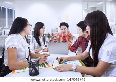 Business team of five people having a meeting in the office - stock photo