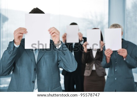 Business team of four holding blank paper copy space