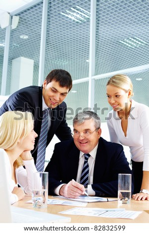 Business team of four people interacting in office at meeting - stock photo
