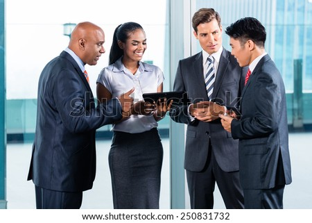 Business team of Indian, Chinese and Caucasian ethnicity discussing in front of city skyline - stock photo