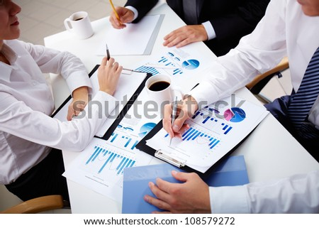 Business team of three analyzing statistical data - stock photo