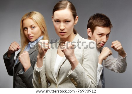Business team of three employees standing in boxing pose - stock photo