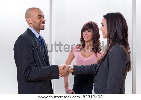 Business team of three, man and woman shaking hands and smiling. - stock photo