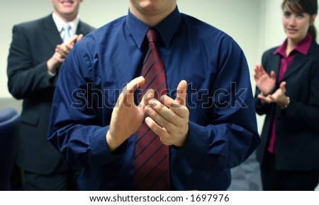 Business team of two men and one woman facing forward and clapping - stock photo