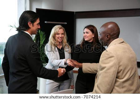 Business Team of workers shaking hands on a deal - stock photo