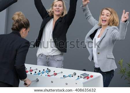 business team playing baby-foot during break time - stock photo