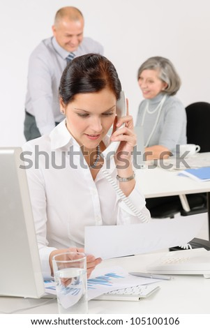 Business team pretty businesswoman calling phone happy colleagues around table - stock photo
