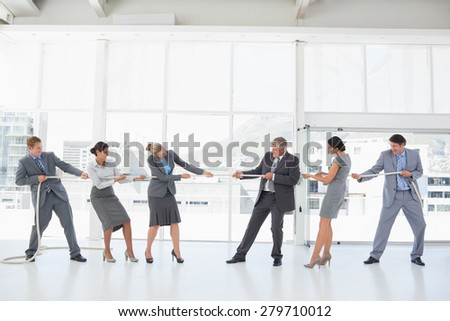 Business team pulling the rope in the office - stock photo
