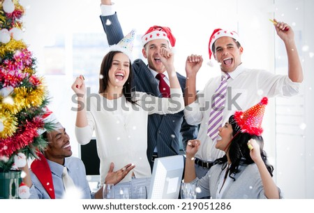 Business team punching the air to celebrate christmas against snow falling - stock photo