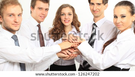 business team putting their hands on top of each other - stock photo