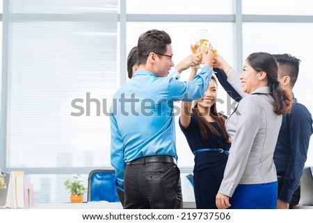 Business team raising glasses to success - stock photo