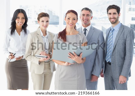 Business team reading from files while taking notes - stock photo