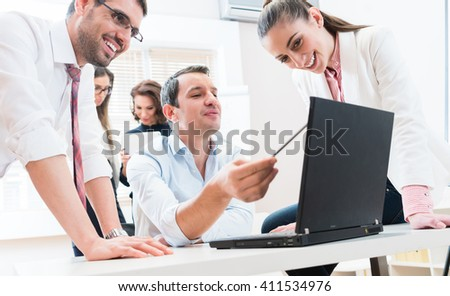 Business team reporting to boss having meeting in office - stock photo