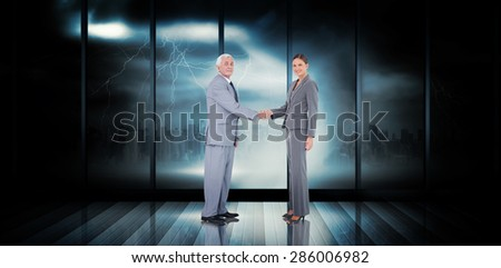 Business team shaking hands against room with large window looking on city - stock photo