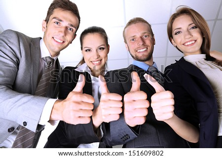 Business team showing thumbs up in office - stock photo