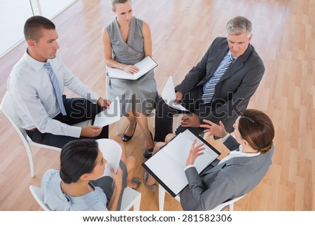 Business team sitting in circle and discussing in the office - stock photo