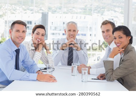 Business team smiling at camera in the office