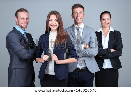 Business team standing in row on grey background - stock photo