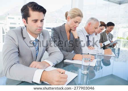 Business team taking notes during conference in the office