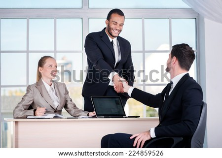 Business team. Three businessman sitting at the table while three businessmen looking at the camera and smiling while standing in office shaking hands with each other - stock photo