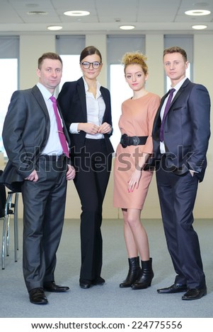 Business team: two men and two beautiful women standing in line in office