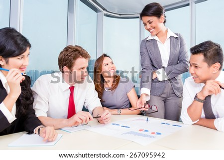 business team with Asian and Caucasian members discussing earnings with financial graphs on the table