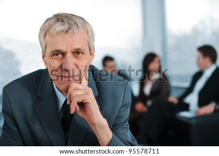 Business team with elderly manager sitting in front - stock photo