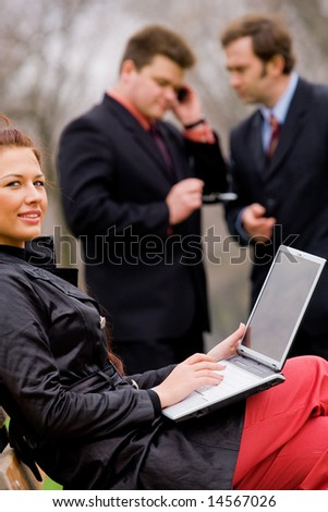 Business team with laptop at outdoor meeting
