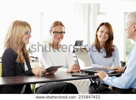 Business team with laptop, working on project while sitting at meeting room. - stock photo