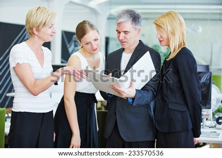 Business team with man and women in office doing planning with files - stock photo