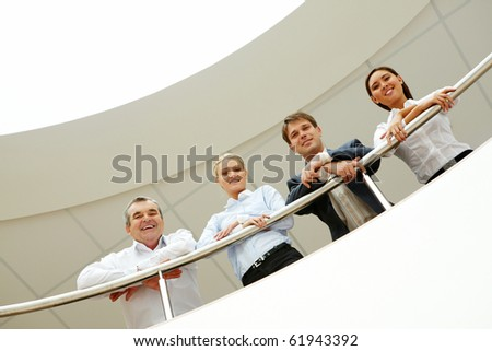 Business team with smiles leaned on the handrail